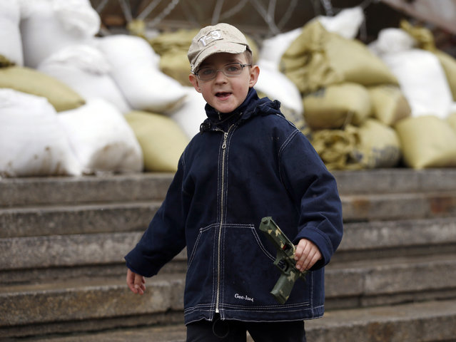 A boy with a toy gun walks in front of seized regional government headquarters in Luhansk, eastern Ukraine, May 2, 2014. Ukrainian forces attacked the rebel-held city of Slaviansk before dawn on Friday and pro-Russia separatists shot down at least one attack helicopter, killing a pilot, in a sharp escalation of the conflict. (Photo by Vasily Fedosenko/Reuters)
