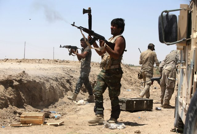 Iraqi Shiite fighters from the Popular Mobilisation units supporting the Iraqi government forces fire towards Islamic State (IS) group positions during clashes on the northern outskirts of the city of Fallujah, west of the capital Baghdad, on July 7, 2015. (Photo by Ahmad Al-Rubaye/AFP Photo)