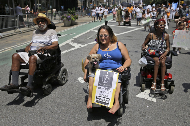 Jessica Delarosa, center, and her dog Mayim participate in the inaugural Disability Pride Parade, Sunday, July 12, 2015, in New York. (Photo by Seth Wenig/AP Photo)