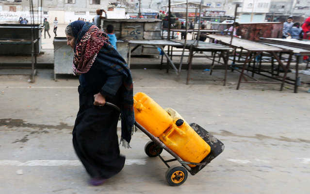 A Palestinian woman drags a cart loaded with water containers after filling them from a public tap in Rafah in the southern Gaza Strip February 28, 2017. (Photo by Ibraheem Abu Mustafa/Reuters)