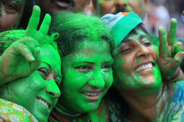 Trinamool Congress Party (TMC) supporters with green faces celebrate the election results near a counting station in Calcutta, India, on May 16, 2014. (Photo by Piyal Adhikary/EPA)