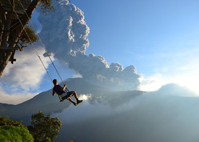 """End of the World"". This photo, taken at the ""end of the world"" swing in Banos, Ecuador, captures a man on the swing overlooking an erupting Mt. Tungurahua. The eruption took place on February 1st, 2014. Minutes after the photo was taken, we had to evacuate the area because of an incoming ash cloud. Photo location: Banos, Ecuador. (Photo and caption by Sean Hacker Teper/National Geographic Photo Contest)"