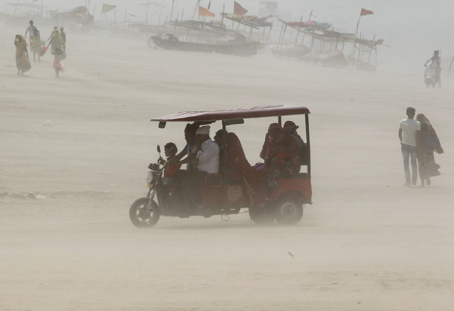 People travel in an auto rickshaw on the banks of the river Ganges during a dust storm in Allahabad, India May 1, 2017. (Photo by Jitendra Prakash/Reuters)