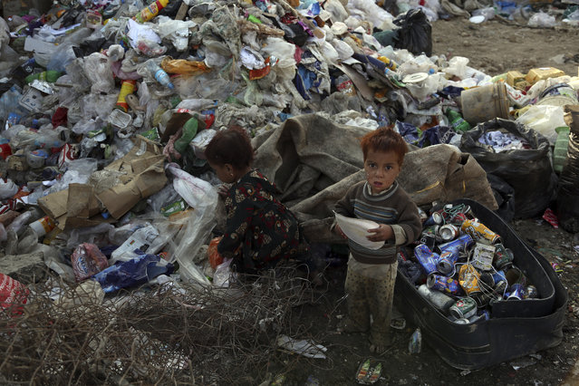An Afghan brother and sister play at a recycling center in Kabul, Afghanistan, Tuesday, October 8, 2019. (Photo by Rahmat Gul/AP Photo)