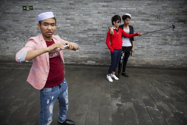 Boys take pictures of themselves as Muslims gather to celebrate Eid al-Fitr at the historic Niujie mosque in Beijing July 18, 2015. The Eid al-Fitr festival marks the end of the holy Muslim fasting month of Ramadan. (Photo by Damir Sagolj/Reuters)