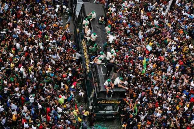 Rugby fans surround the bus of the South African Springbok rugby team, during a victory parade in downtown Johannesburg, South Africa, Thursday, November 7, 2019. South Africa's Rugby World Cup-winning team has started a five-day victory tour where they will carry the trophy across the country. (Photo by Denis Farrell/AP Photo)