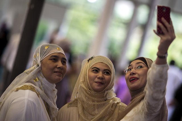 Thai Muslim women take a selfie after they attend a mass prayer during Eid al-Fitr celebrations at a mosque in Bangkok, Thailand, July 17, 2015. (Photo by Athit Perawongmetha/Reuters)