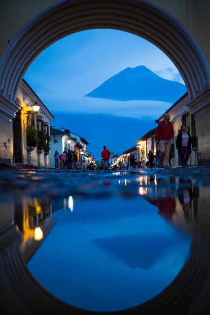 """""""Twin Peaks of Antigua"""". The shadow of night is cast over Antigua as Volcán de Agua's silhouette dominates the horizon through Santa Catalina Arch, reflecting in the cobblestone rain puddles. Photo location: Santa Catalina Arch, Antigua, Guatemala. (Photo and caption by Beau Pilgrim/National Geographic Photo Contest)"""