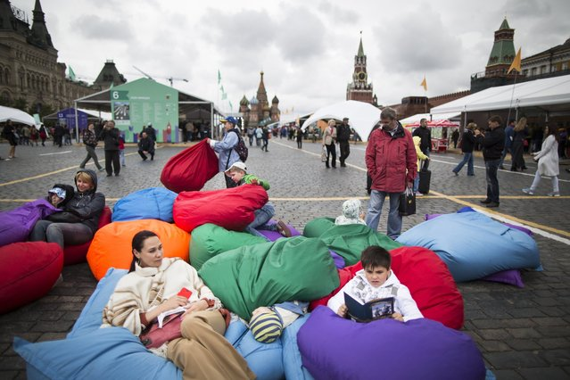 Visitors relax on bean bags during a book festival in Red Square with the St. Basil's Cathedral, center, and the Spasskaya Tower, right, in the background in Moscow, Russia, Monday, June 6, 2016. Held for the first time last year, the book festival was a great success that attracted 200,000 visitors, but this year there will be even more activities and, the organizers hope, bigger numbers. (Photo by Alexander Zemlianichenko/AP Photo)