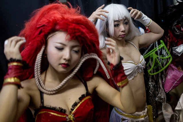 Performers  change into their costumes backstage prior to the start of a show at The Robot Restaurant on June 29, 2014 in Tokyo, Japan. The now famous Robot Restaurant opened two years ago in Kabukicho area of Shinjuku at an estimated cost of 10 million U.S. dollars.  Performances are held three times a day and cater mostly to foreign tourists. (Photo by Chris McGrath/Getty Images)