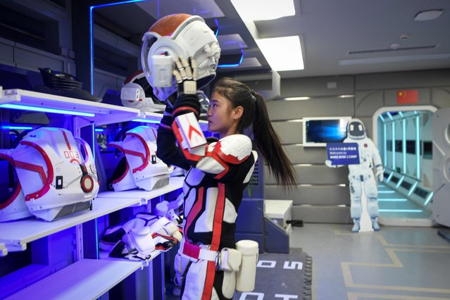 """A guide wearing a spacesuit puts on a helmet at """"Mars Base 1"""", a C-Space Project, in the Gobi desert, some 40 kilometres from Jinchang in China's northwest Gansu province on April 17, 2019. Surrounded by barren hills in northwest Gansu province, """"Mars Base 1"""" opened to the public on April 17 with the aim of exposing teens – and soon tourists – to what life could be like on the planet. (Photo by Wang Zhao/AFP Photo)"""