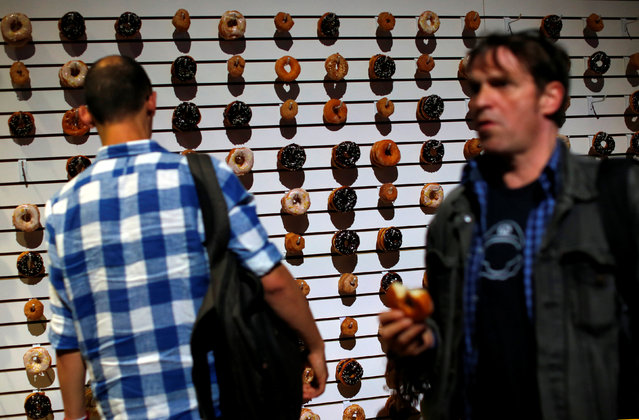 People walk past and grab free donuts hanging from a wall display as they attend Sony Corporation's PlayStation 4 E3 2016 event in Los Angeles, California, U.S. June 13, 2016. (Photo by Mike Blake/Reuters)