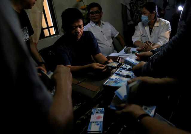 Members of the National Bureau of Investigation count cash found in the home of a police officer and member of the drugs unit, during a raid in metro Manila, Philippines May 25, 2016. (Photo by Romeo Ranoco/Reuters)