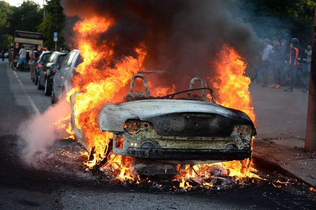"""A car burns during the demonstration """"G20 Welcome to hell"""" in Hamburg, Germany, 06 July 2017. The G20 Summit of the heads of government and state takes place on 7 and 8 July 2017 in Hamburg. (Photo by Christophe Gateau/DPA)"""