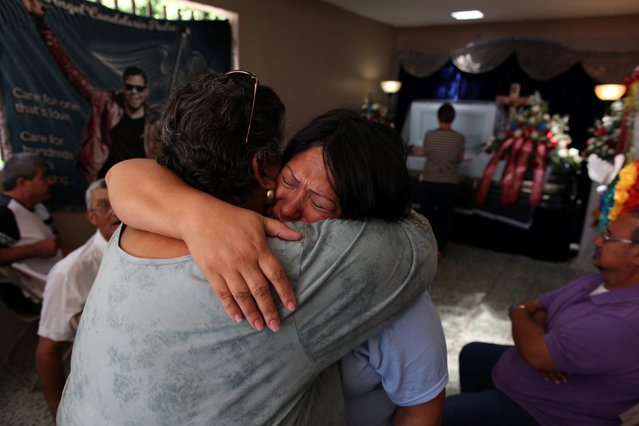 The body of Angel Candelario, one of the victims of the shooting at the Pulse night club in Orlando, lies in a coffin as family and friends mourn at his wake in his hometown of Guanica, Puerto Rico, June 17, 2016. (Photo by Alvin Baez/Reuters)