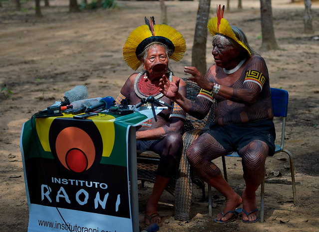 Indigenous leader Cacique Raoni of the Kayapo tribe (L) and an interpreter speak in Piaracu village, near Sao Jose do Xingu, Mato Grosso state, Brazil, on January 15, 2020. Brazil's government will propose legalizing oil and gas exploration as well as hydroelectric dam construction on indigenous land, a report said Saturday, citing a draft of a bill to be sent to Congress. (Photo by Carl de Souza/AFP Photo)