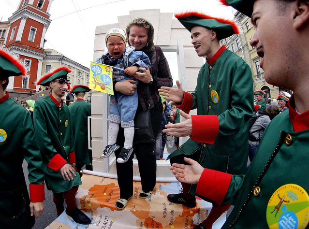 A woman and her child walk through a symbolic Window to Europe during celebrations marking the 309th anniversary of the city of St.Petersburg, Russia on May 26, 2012