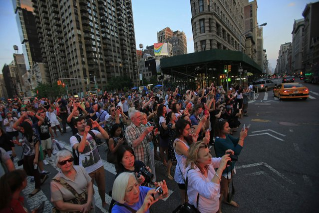 """People take pictures at sunset, during the bi-annual occurrence """"Manhattanhenge"""" in New York July 11, 2014. Manhattanhenge, coined by astrophysicist Neil deGrasse Tyson, occurs when the setting sun aligns itself with the east-west grid of streets in Manhattan, allowing the sun to shine down all streets at the same time. (Photo by Eduardo Munoz/Reuters)"""