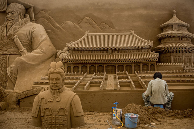 Sand sculptor Zhang Weikang of China works on the Chinese section of a large sand sculpture at the site of Yokohama Sand Art Exhibition – Culture City of East Asia 2014 on July 16, 2014 in Yokohama, Japan. Producer and sand sculptor Katsuhiko Chaen invited artists from around the world including South Korea and China, to recreate the World Heritage and historical buildings in China, Japan and South Korea. The exhibition will be open from July 19 to November 3, 2014. (Photo by Chris McGrath/Getty Images)