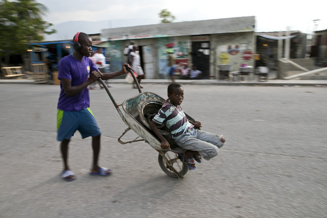 In this December 3, 2019 photo, a young man pushes a wheelbarrow home as his little brother takes a ride on it, in the Cite Soleil slum of Port-au-Prince, Haiti. The two youths are going home after helping their mother by carrying items to sell in the market. In the last two years, Haiti's currency, the gourde, declined 60% against the dollar and inflation recently reached 20%. (Photo by Dieu Nalio Chery/AP Photo)