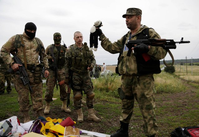A pro-Russian fighter holds up a toy found among the debris at the crash site of a Malaysia Airlines jet near the village of Hrabove, Friday, July 18, 2014. Emergency workers, police officers and even off-duty coal miners spread out Friday across the sunflower fields and villages of eastern Ukraine, searching the wreckage of a Malaysia Airlines jet shot down as it flew high above the country's battlefield. The attack Thursday afternoon killed 298 people from nearly a dozen nations. (Photo by Dmitry Lovetsky/AP Photo)