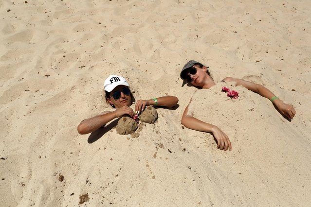 Russian tourits are are buried in the hot sand as they relax at the beachside of the Imperial Marhaba hotel which was attacked by a gunman last year in Sousse, Tunisia June 26, 2016. (Photo by Zohra Bensemra/Reuters)