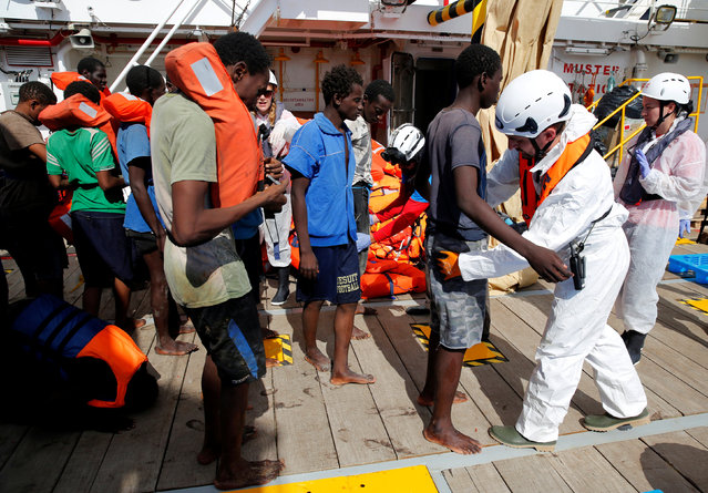 Migrants are searched by Migrant Offshore Aid Station (MOAS) personnel after boarding the MOAS rescue ship Topaz Responder around 20 nautical miles off the coast of Libya, June 23, 2016. (Photo by Darrin Zammit Lupi/Reuters)