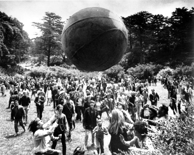 """A crowd keeps a large ball, painted to represent a world globe, in the air during a gathering at Golden Gate Park in San Francisco, to celebrate the summer solstice on Thursday, June 21, 1967, day one of """"Summer of Love"""". If the Summer of Love established San Francisco as the hub of hippiedom, the summer of 2007 may one day be remembered as a time when the city and the rest of the country commemorated 1960s counterculture by taking the """"counter"""" out of it. (Photo by AP Photo)"""