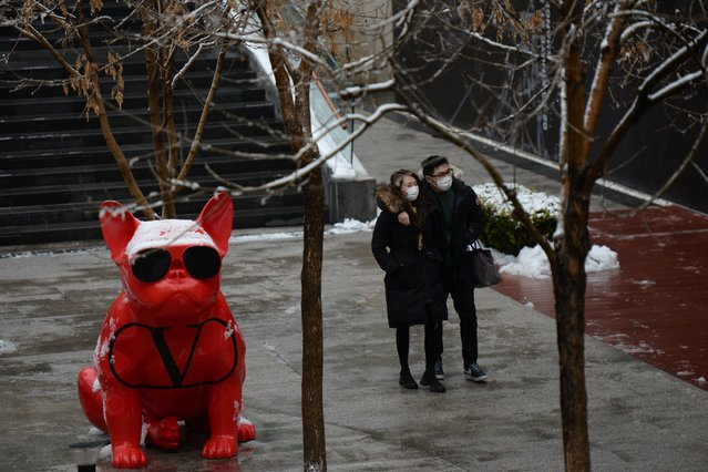 A couple wearing face masks walks at the Sanlitun shopping area amid snowfall, following an outbreak of the novel coronavirus in the country, on Valentine's Day in Beijing, China on February 14, 2020. (Photo by Tingshu Wang/Reuters)