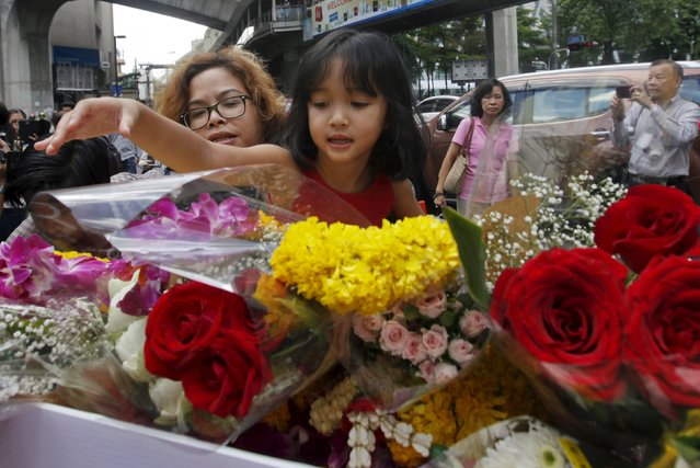 A girl places a flower at the Erawan shrine, the site of Monday's deadly blast, in central Bangkok, Thailand, August 19, 2015. (Photo by Kerek Wongsa/Reuters)