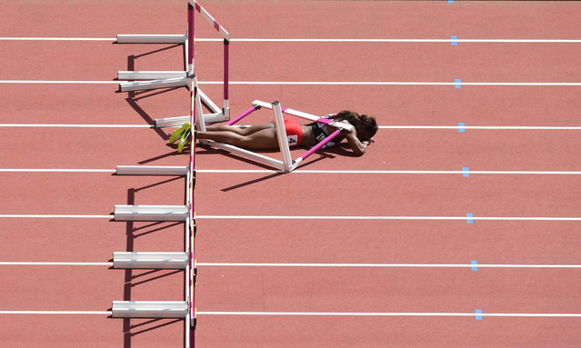Trinidad and Tobago's Deborah John lies on the track after falling in the women's 100m hurdles athletics event at the 2017 IAAF World Championships at the London Stadium in London on August 11, 2017. (Photo by Glyn Kirk/AFP Photo)