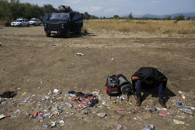 Macedonian police block migrants at no-man's land between Greece and Macedonia near the southern Macedonian town of Gevgelija, Thursday, August 20, 2015. (Photo by Darko Vojinovic/AP Photo)