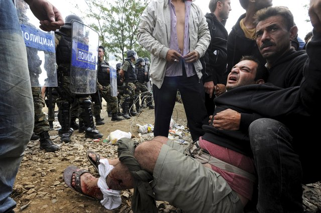 A migrant reacts after he was injured during clashes with Macedonian police at the Greek-Macedonian border, August 21, 2015. (Photo by Alexandros Avramidis/Reuters)