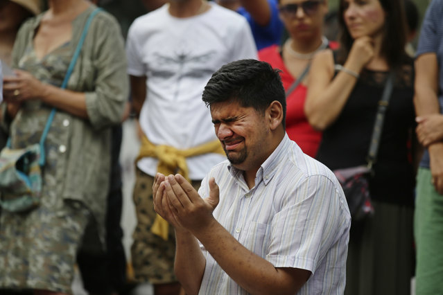 A man cries as he prays by a memorial tribute to the van attack victims in Barcelona, Spain, Saturday, August 19, 2017. Authorities in Spain and France pressed the search Saturday for the supposed ringleader of an Islamic extremist cell that carried out vehicle attacks in Barcelona and a seaside resort, as the investigation focused on links among the Moroccan members and the house where they plotted the carnage. (Photo by Manu Fernandez/AP Photo)