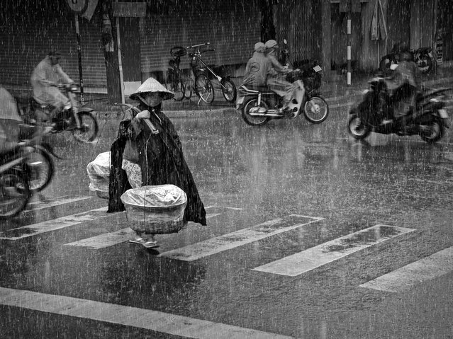 CGAP Photo Contest – First Prize: Rainy Afternoon, Vietnam. A woman transports potatoes to a local market. Her earnings help feed two children and her husband. After a sunny day, the rain poured down suddenly. (Photo by Truong Minh Dien)