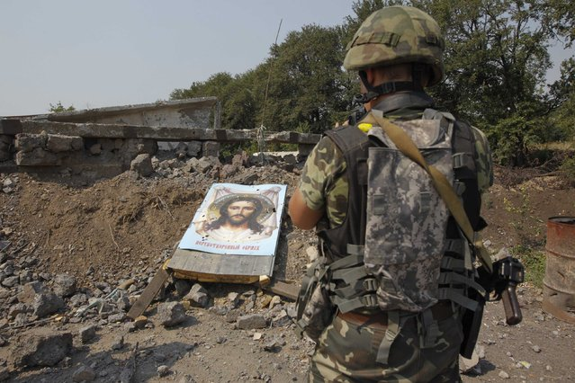 A Ukrainian serviceman stands near a damaged board with an image of Jesus Christ, which was left by pro-Russian separatists, at a check point in the town of Vuhlehirsk, Donetsk region, August 14, 2014. (Photo by Valentyn Ogirenko/Reuters)
