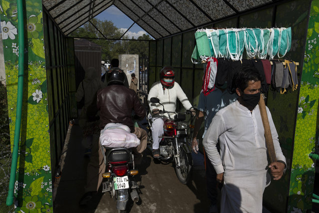 People move through a disinfecting tunnel at a vegetable and fruit market as government-imposed a nationwide lockdown to contain the outbreak of the coronavirus, in Islamabad, Pakistan, Thursday, April 2, 2020. (Photo by B.K. Bangash/AP Photo)