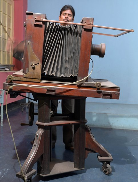 Indian worker, Sandip Ghaosh adjusts a 174-year old Wet Plate Camera manufactured by W. Watson & Son, London inside the century-old Bourne and Shepherd studio on World Photography Day in Kolkata on August 19, 2014. (Photo by Dibyangshu Sarkar/AFP Photo)