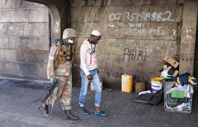 A member of the South African National Defense Force escorts a homeless man during the first day of a nationwide lockdown for 21 days to try to contain the coronavirus disease outbreak, in Johannesburg, South Africa, March 27, 2020. (Photo by Siphiwe Sibeko/Reuters)