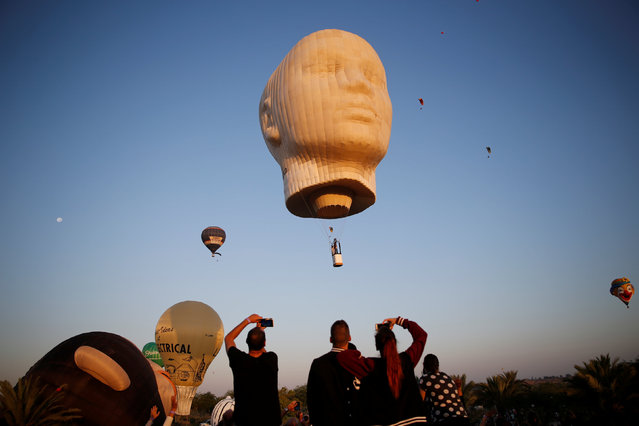 People are seen watching hot air balloons fly overhead during a two-day international hot air balloon festival in Eshkol Park near the southern city of Netivot, Israel July 22, 2016. (Photo by Amir Cohen/Reuters)