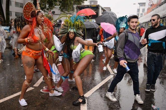 Performers dance during the second day of the Notting Hill Carnival in London, on August 25, 2014. The event honors the city's Afro-Caribbean culture in an area that has been home to thousands of Caribbean immigrants since the 1950s. (Photo by Leon Neal/AFP Photo)