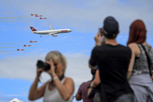 "An Airbus A330 commercial plane of Swiss International Air Lines flies with fighter jets of the ""Patrouille Suisse"" (Swiss patrol) on August 30, 2014 during the first day of AIR14 airshow in Payerne, western Switzerland. The airshow commemorates over two weekends the 100th anniversary of the Swiss Air Forces. (Photo by Fabrice Coffrini/AFP Photo)"