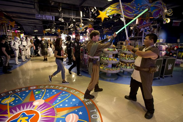 """People dressed as characters from """"Star Wars"""" interact with their toy lightsabers as shoppers carry bags of purchases after toys went on sale at midnight in advance of the film """"Star Wars: The Force Awakens"""" in Times Square in the Manhattan borough of New York, September 4, 2015. (Photo by Carlo Allegri/Reuters)"""