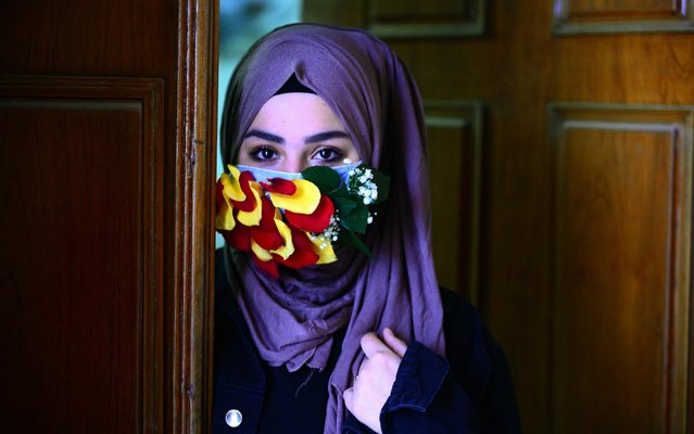 A woman is seen wearing a mask embellished with petals in the central Iraqi holy city of Najaf on March 21, 2020 amid the COVID-19 coronavirus pandemic. (Photo by Haidar Hamdani/AFP Photo)
