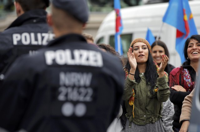 German police stand in front of protesters against Turkish President Tayyip Erdogan during a pro-government protest in Cologne, Germany July 31, 2016. (Photo by Vincent Kessler/Reuters)