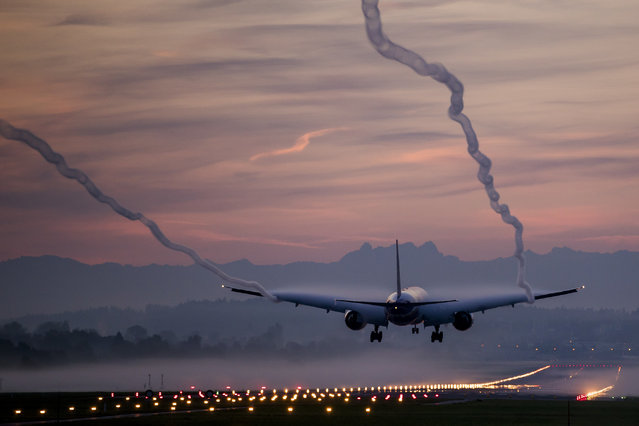 A Boeing 777-300 from Swiss International Airlines lands on a foggy morning at Zurich Airport, on Friday, October 13, 2017, in Zurich, Switzerland. The high humidity renders the air vortex visible. (Photo by Christian Merz/Keystone via AP Photo)