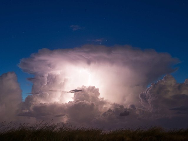 Lightning illuminates a thundercloud as a storm front hits the North Sea region near Westerhever, northern Germany, on August 11, 2014. (Photo by Daniel Reinhardt/AFP Photo/DPA)