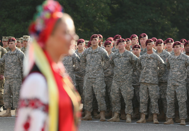 "Members of the U.S. Army 173rd Airborne Brigade stand at attention as a Ukrainian folk dance group performs at the opening ceremony of the ""Rapid Trident"" NATO military exercises on September 15, 2014 near Yavorov, Ukraine. (Photo by Sean Gallup/Getty Images)"