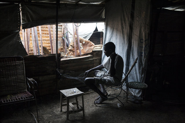 A man weaves a fishing net in his shelter in the  Protection of Civilians (POC) site at the United Nations Mission in South Sudan (UNMISS) compound in Malakal, South Sudan on Wednesday, July 13, 2016. (Photo by Jane Hahn/The Washington Post)