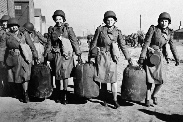 Women help each other with bags at an embarkation port in the U.S. in this January 29, 1943, photo provided by the U.S. Army. They were bound for North Africa with the first detachment of the Women's Auxiliary Army Corps to be sent abroad. (Photo by AP Photo)